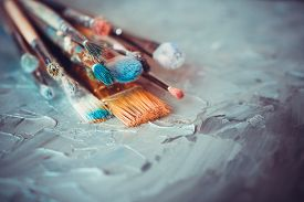 stock photo of canvas  - Paintbrushes on artist canvas covered with oil paints - JPG
