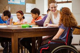 stock photo of teachers  - Teacher helping a disabled pupil at the elementary school - JPG