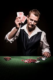pic of gambler  - A male gambler is frustrated after losing and throw the cards away showing movement - JPG