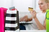 stock photo of antidepressant  - Blond woman making purchasing via internet paying credit card. Focus on fresh buyings packed in colored paper bags standing in front of her. Shopping consumerism delivery and present concept ** Note: Shallow depth of field - JPG