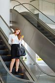 stock photo of escalator  - Businesswoman going down the escalator and reading a text message on her smart phone - JPG