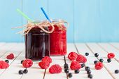stock photo of mason  - Rustic Mason Jars with raspberry jam and bog bilberry marmalade with fresh berries on white wooden background - JPG