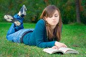 stock photo of girl reading book  - student reading a book in the city park skopje - JPG