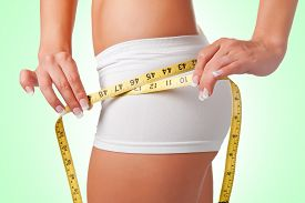 image of measurement  - Woman measuring her waist with a yellow measuring tape - JPG