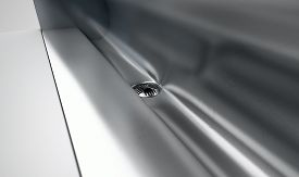 image of urinate  - A a closeup of the drain of a stainless steel trough style urinal on an isolated white studio background - JPG