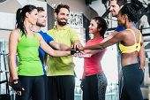 Woman and men being motivated for fitness and sport stacking their hands poster