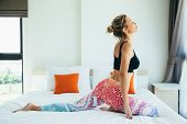 Woman doing yoga exercise on bed at home. Morning workout in bedroom. Healthy and sport lifestyle. poster