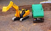 picture of dumper  - Green dumper and yellow excavator on a road building - JPG