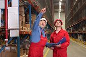 two inspectors in uniforms and hardhats in warehouse