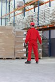stock photo of workplace safety  - worker in red uniform with bar code reader preparing to work in warehouse - JPG