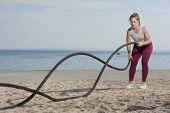 Young Attractive Sportive Woman Battling Ropes Doing A Workout Exercise On A Beach. Sportive Woman I poster