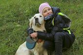 Dog Playing With Owner. Young Girl Playing With Her Pet Golden Retriever. Dog And Owner, Outdoor. Go poster