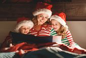 Merry Christmas! Family Mother Reads To Children A Book Before Bed In Bed poster