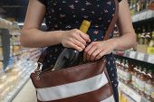 Woman Is Stealing Bottle Of Wine And Hiding It In Handbag In Supermarket. poster
