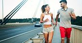 Athletic Young Cute Couple Jogging Together Outdoors poster