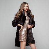 Fashion Portrait Young Woman In Black Fur Coat. Girl With Elegant Hairstyle Posing On A Gray Backgro poster