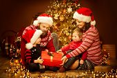 Christmas Family Opening Present, Xmas Tree And Gifts, Happy Father Mother Child And Baby In Sweater poster