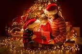 Christmas Family Opening Lighting Present Gift Box Under Xmas Tree, Happy Mother And Children In Mag poster