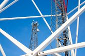 Metal Structures Of Cell Tower Against A Blue Sky. Ladder, Support Towers And Metal Construction Of  poster