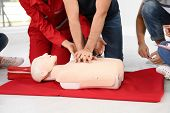 Group Of People With Instructor Practicing Cpr On Mannequin At First Aid Class Indoors, Closeup poster