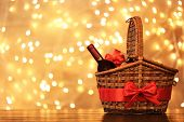 Gift Basket With Bottle Of Wine Against Blurred Lights. Space For Text poster