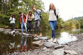 Multi ethnic group of five young adult friends hold hands walking on rocks to cross a stream during  poster