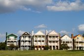 stock photo of memphis tennessee  - Upscale townhomes for the wealthy built on a grass hill in a row against a cloudy blue sky in Memphis Tennessee - JPG