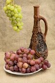 image of loamy  - Ceramic bottle and grapes on the sacking background - JPG