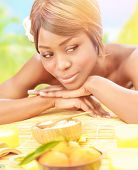 Attractive black woman relaxed on luxury spa resort, lying down on massage table with frangipani flo