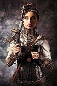 foto of steampunk  - Portrait of a beautiful steampunk woman holding a gun over grunge background - JPG