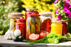stock photo of jar jelly  - Jars of pickled vegetables in the garden. Marinated food ** Note: Shallow depth of field - JPG