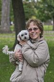 stock photo of maltipoo  - Adult Woman With Her Maltipoo Puppy At The Park - JPG