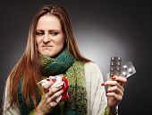 stock photo of paracetamol  - Studio shot of a woman holding a cup of hot tea and expressing disgust to some blister packed tablets she is holding over gray background - JPG