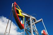 stock photo of nonrenewable  - Oil pump jack against blue sky background - JPG