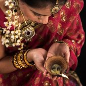 stock photo of sari  - Beautiful Indian female hands holding diya oil lamp - JPG