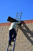 pic of osha  - A roofing company worker climbs a high ladder to the top of a building holding a heavy roll of tarpaper - JPG