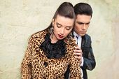 image of cold-shoulder  - Fashion woman looking down while her boyfriend is touching her shoulder with his hand - JPG