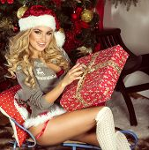 image of christmas claus  - Sexy beautiful blonde woman posing in Santa Claus costume at home - JPG