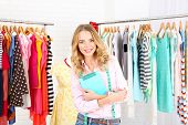 stock photo of racks  - Beautiful young stylist near rack with hangers - JPG
