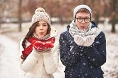 picture of blowing  - Portrait of cute young dates in casual winterwear blowing snowflakes from palms  - JPG