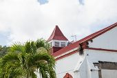 stock photo of red roof tile  - An old white plaster building with a red tile roof in the tropics with palm tree - JPG