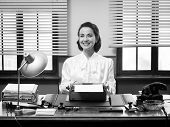 foto of old lady  - Cheerful vintage secretary working at office desk and smiling at camera