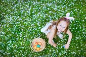 stock photo of easter eggs bunny  - Above view of adorable little girl wearing bunny ears playing with Easter eggs on a grass covered with white flower petals on spring day - JPG