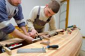 pic of canoe boat man  - Young carpenter sanding new canoe in workshop - JPG