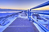 stock photo of windswept  - Lonely windswept pier on the frozen Great Lakes coast - JPG