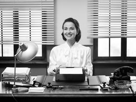 foto of secretary  - Cheerful vintage secretary working at office desk and smiling at camera