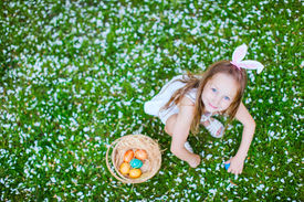 stock photo of bunny costume  - Above view of adorable little girl wearing bunny ears playing with Easter eggs on a grass covered with white flower petals on spring day - JPG