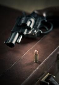 foto of revolver  - Vintage revolver gun on leather briefcase with bullet close - JPG