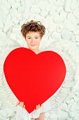 foto of cupid  - Portrait of a lovely emotional little boy in a costume of angel holding red hearts - JPG