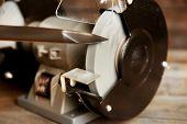 stock photo of friction  - Knife sharpener on wooden table - JPG